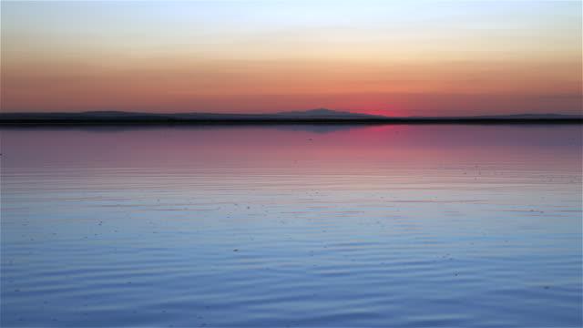 太陽がゆっくりと沈む湖 - 水面点の映像素材/bロール