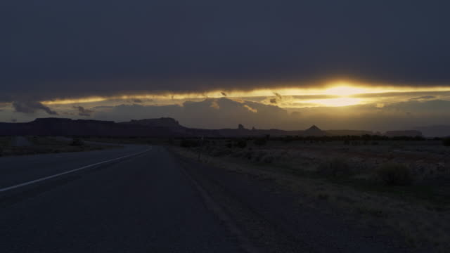 The sunset in the highland desert over the highway US-70 nearby Green River, Utah, USA