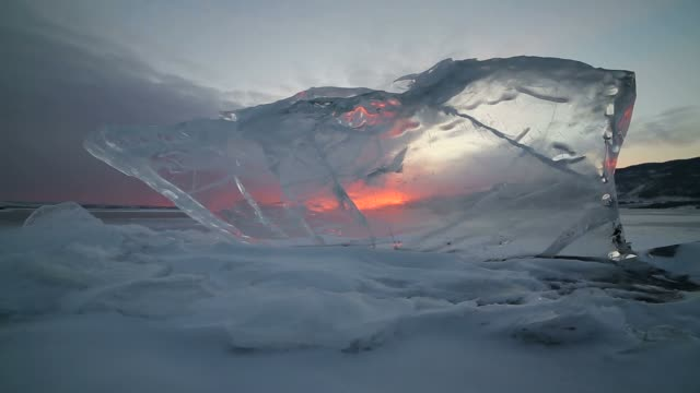 the sunset through the transparent ice in motion - ghiaccio galleggiante video stock e b–roll