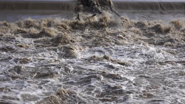 vídeos de stock, filmes e b-roll de a superfície do fluxo rápido da água suja durante uma inundação - erodido