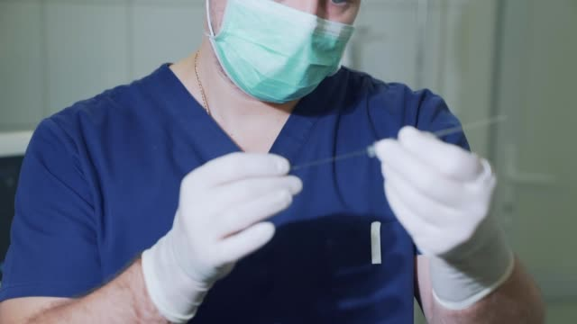 the surgeon demonstrates a large metal needle. the doctor examines medical equipment in sterile gloves. needle for shunting of varicose veins - lama oggetto creato dall'uomo video stock e b–roll