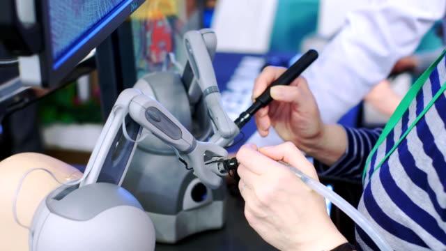vídeos y material grabado en eventos de stock de el cirujano realiza una operación en realidad virtual. nuevas tecnologías en cirugía. cirujano que opera la máquina de cirugía robótica médica. control manual por sistema quirúrgico mínimamente invasivo - arteriograma