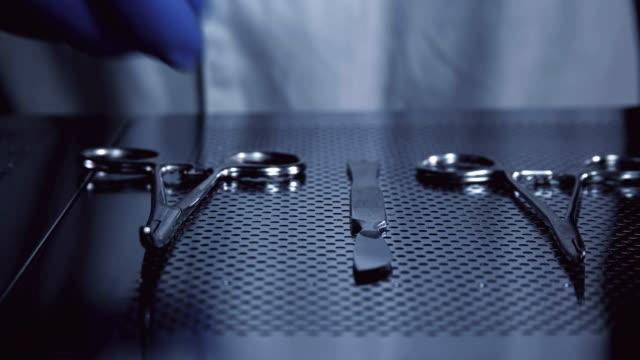 vídeos y material grabado en eventos de stock de el cirujano toma un bisturí de la tabla con las herramientas para la operación - cuchillo cubertería