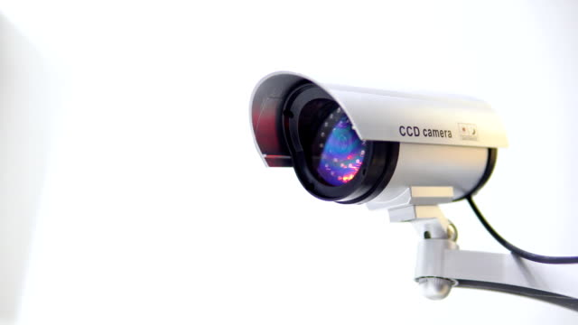 The surveillance camera with flashing red light on white background. Close up video
