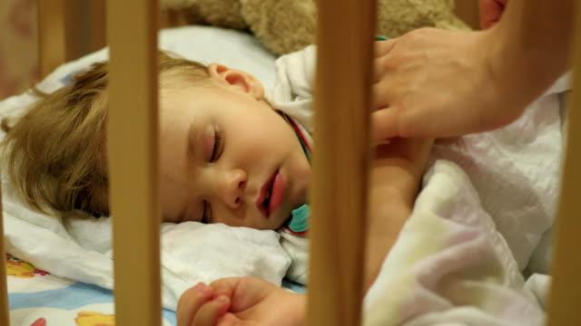 stockvideo's en b-roll-footage met de zoete baby slaapt in een kinderbed. moeder heeft betrekking op een deken - sleeping illustration