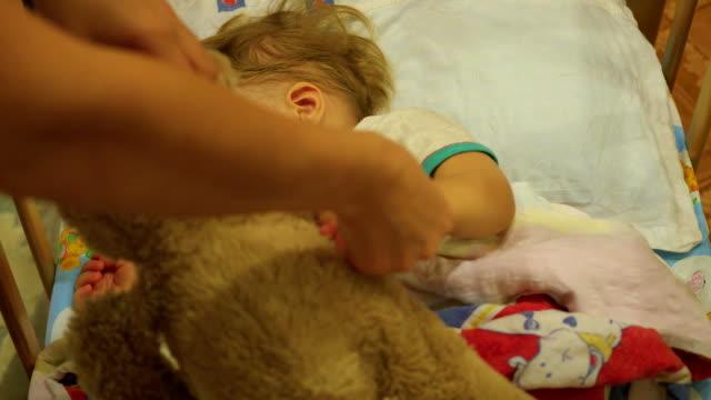 stockvideo's en b-roll-footage met de zoete baby slaapt in een bed met een teddybeer. moeder beweegt een teddybeer - sleeping illustration