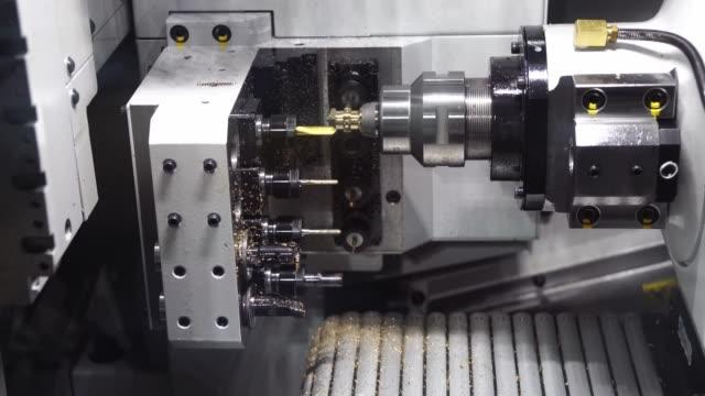 den schweiziska cnc svarvmaskinen av typen cnc gör mässingskontaktdelarna för luftkonditioneringsdelar. - svarv bildbanksvideor och videomaterial från bakom kulisserna