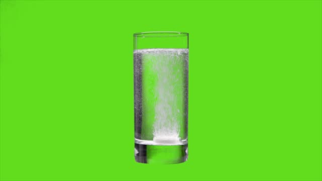 the tablet dissolves in water on an green screen - dissolvere video stock e b–roll