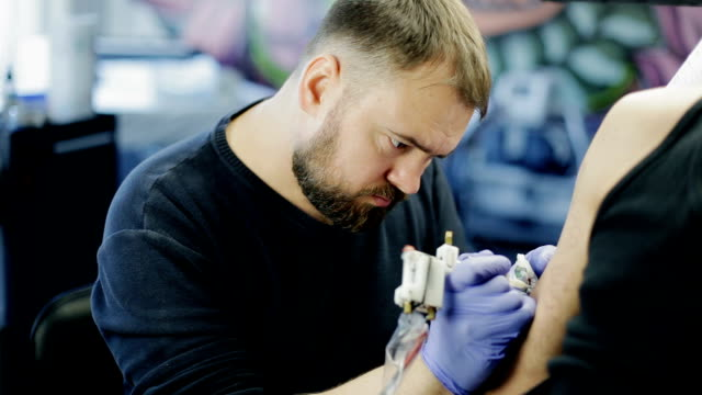 The tattoo artist at work. Apply a pattern on the customer's shoulder. video