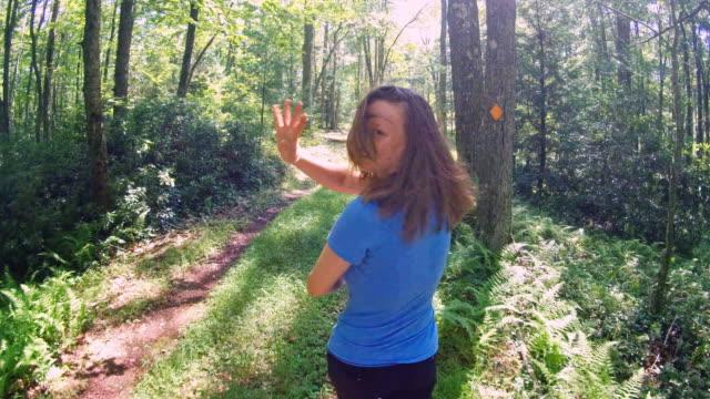 l'adolescente 16enne caucasica bianca, dai capelli lunghi, ragazza che fa escursioni sul sentiero della foresta, guardando indietro e salutando. - hickory run video stock e b–roll