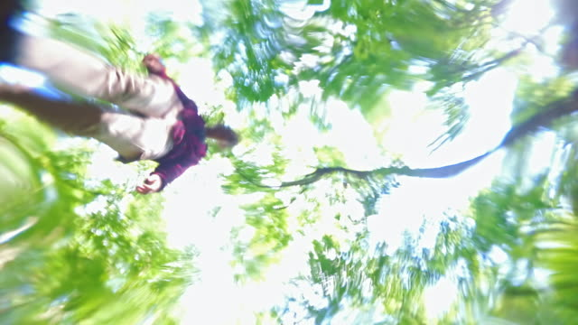 The teenage girl jumping over the brook in the forest. Unusual point of view upside-down, looking upward from the bottom of the flow through the water surface. video