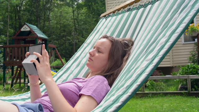 The teenage girl reading in the hammock video