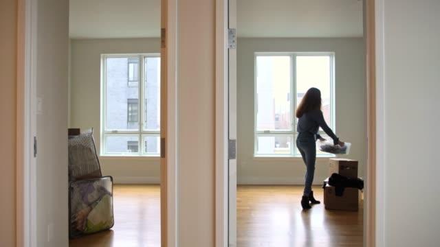 La fille adolescente, déplacez les boîtes dans le nouvel appartement vide - Vidéo