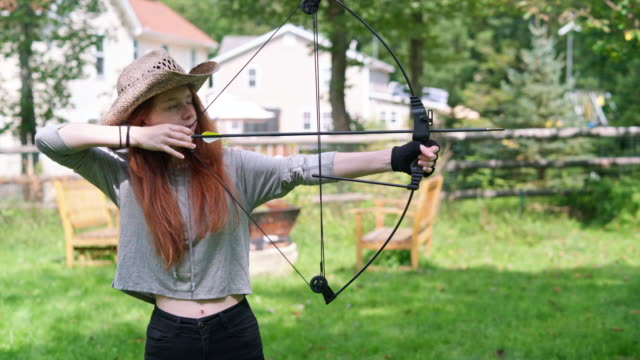 The teenager girl shooting a bow, practicing archery at the backyard video