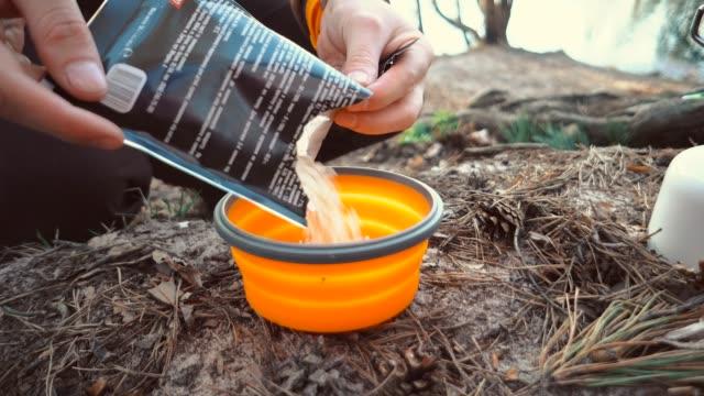 das thema tourismus ist wandern und reisen in der natur. hände kaukasischen mann gießt trockener trockenfutter in einem teller zum kochen. thema essen unter campingbedingungen, essen auf dem campingplatz - dampfkochen stock-videos und b-roll-filmmaterial