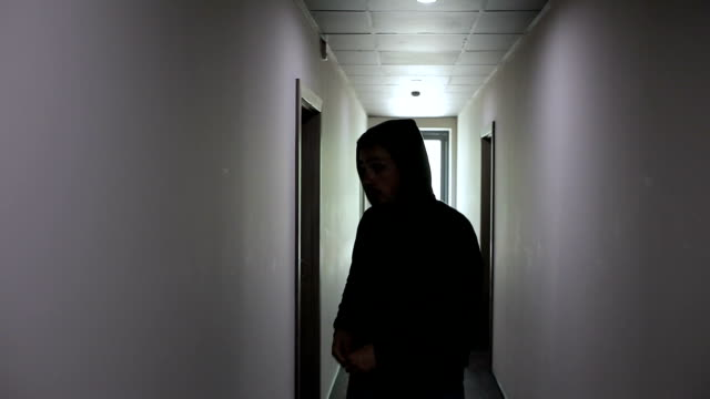 The thief steals along the corridor and breaks the door of the apartment video