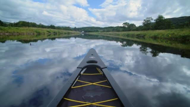 la punta della barca che naviga attraverso il canale caledoniano sotto un cielo blu chiaro. -colpo largo - fort william video stock e b–roll