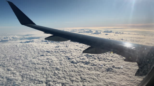 The Tops of Clouds from over the Wing of an Airliner Jet on a Sunny Day