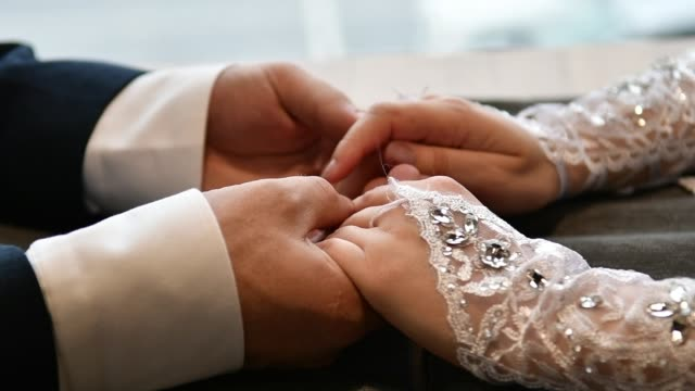 the touch of the hands of the bride and groom. - mano donna dita unite video stock e b–roll