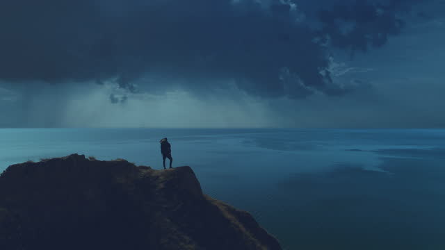 The tourist is standing on the mountain cliff on the night seascape background