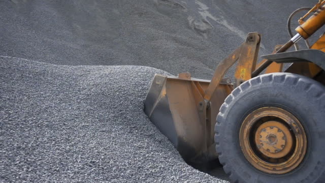 the tractor collects a scoop with gravel. stock footage. side view of an excavator loading its bucket with crushed stones or rubble at the construction site - {{asset.href}} video stock e b–roll