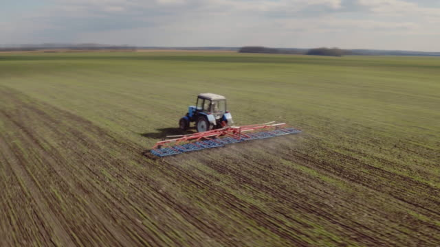 The tractor cultivates the land in the field in early spring. The camera flies around video