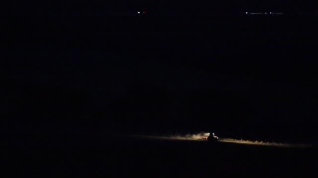 vídeos de stock e filmes b-roll de the tractor is driving through the night field - colher atividade agrícola