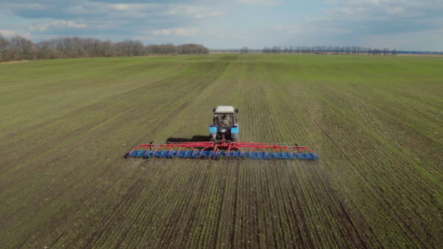 The tractor is working in the field in early spring. Produces harrowing to prevent soil loss of moisture. 4K aerial video video