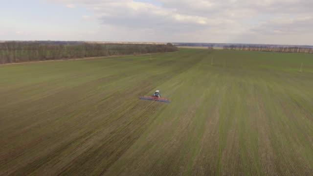 The tractor is working in the field in early spring - the long-range plan, aerial survey video