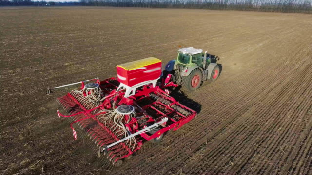 The tractor pulls a large seeder across the field. Sowing campaign in early spring, rural landscape. Concept - modern agribusiness video