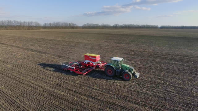 The tractor pulls a large seeder across the field. Sowing campaign in early spring, rural landscape. Side view. Concept - modern agribusiness video