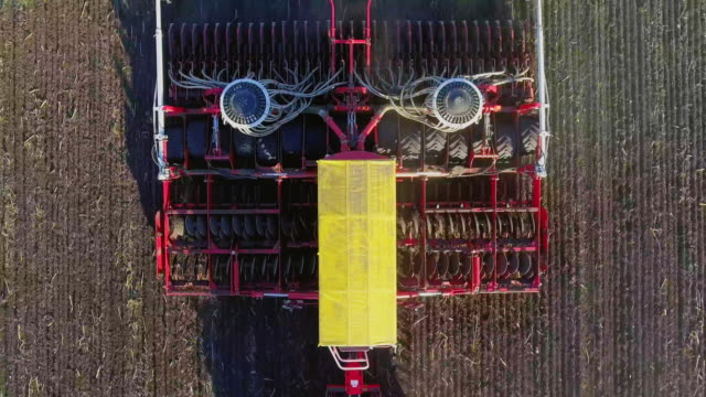 The tractor pulls a large seeder across the field. Sowing campaign in early spring, rural landscape. Top view. Concept - modern agribusiness video