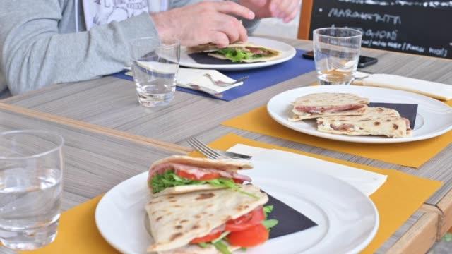 çeşitli dolgular ile emilia romanya bölgesinin geleneksel i̇talyan piadina. garson masaya tabak ve öğle yemeği getirdi. bir i̇talyan restoranında öğle yemeği. - ravenna stok videoları ve detay görüntü çekimi