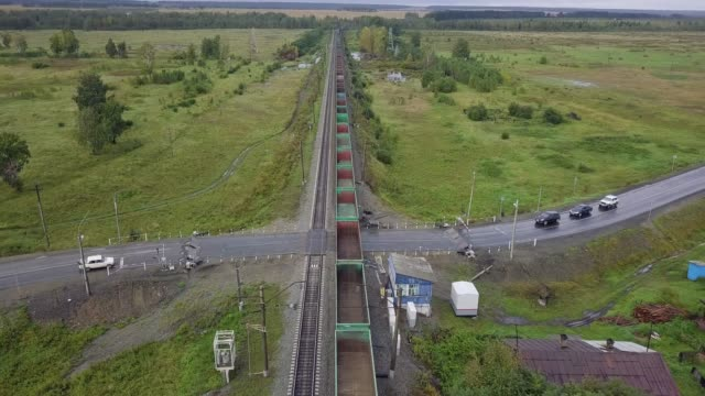 vídeos de stock e filmes b-roll de the train rides at the railway crossing. shooting from a drone - encruzilhada