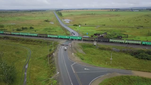 The train rides at the railway crossing. Shooting from a drone
