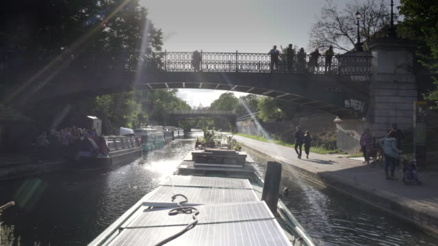 the tranquil veiw from a narrow boat as it passes through regents park - canale video stock e b–roll