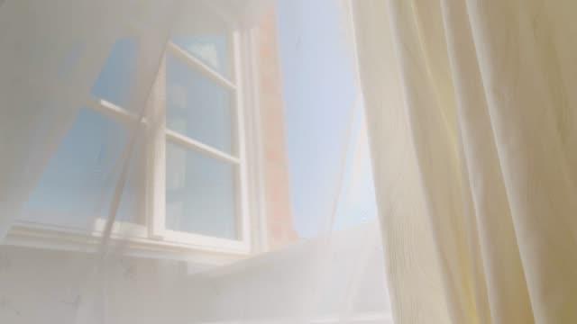 vídeos de stock, filmes e b-roll de a cortina transparente funde no vento do verão na janela aberta - janela
