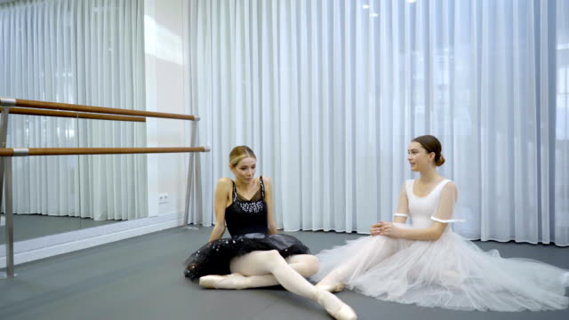 The two ballerinas sit on the floor in the bright studion during the break on repetition video