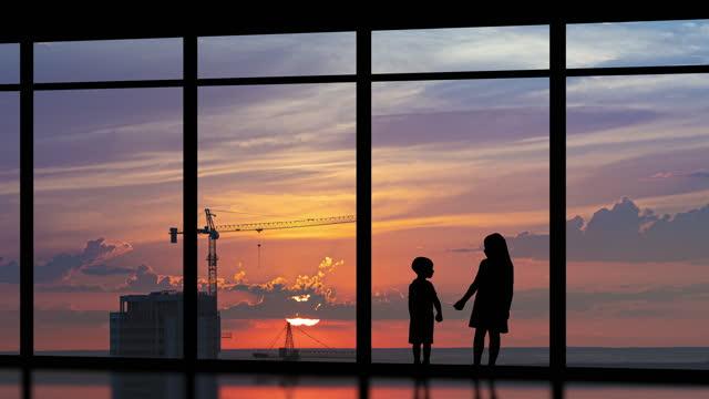 二人の子供たちは建物の背景の大きな窓の近くに立っています。タイムラプス - クレーン点の映像素材/bロール