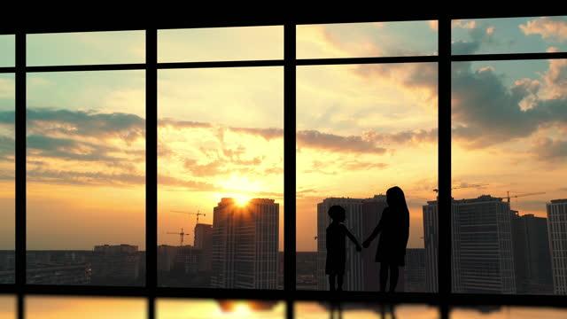 二人の子供たちは、建物の背景に大きな窓の近くに立っています - クレーン点の映像素材/bロール