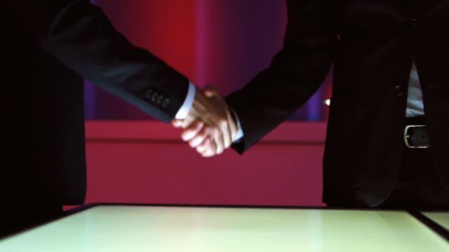 大きなディスプレイの近く 2 人の握手。スローモーション - 合意点の映像素材/bロール