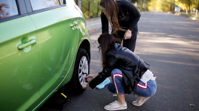The two women using jack-screw to lift a car before changing flat tire on dirt road at countryside