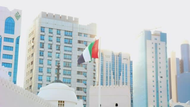 the united arab emirates flag waving around city skyline against the shiny sun - uae national day стоковые видео и кадры b-roll