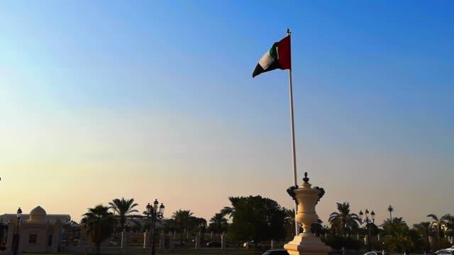 sharjah şehirde günbatımında sallayarak birleşik arap emirlikleri bayrağı - uae flag stok videoları ve detay görüntü çekimi