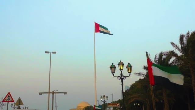 the united arab emirates flags waving at sunset around abu dhabi city streets - uae flag filmów i materiałów b-roll