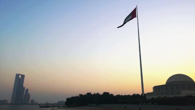 gün batımında abu dabi şehir içinde sallayarak birleşik arap emirlikleri bayrağı - uae flag stok videoları ve detay görüntü çekimi