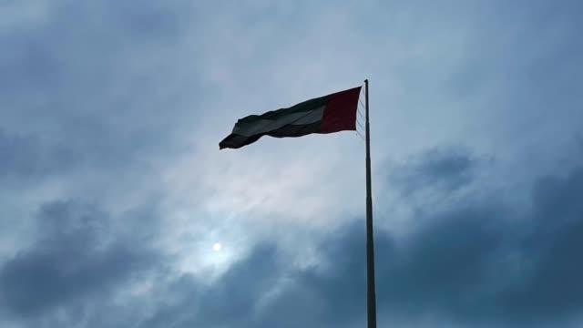 abu dabi şehir - bulutlar ve güneş ışığı sallayarak birleşik arap emirlikleri bayrağı - uae flag stok videoları ve detay görüntü çekimi