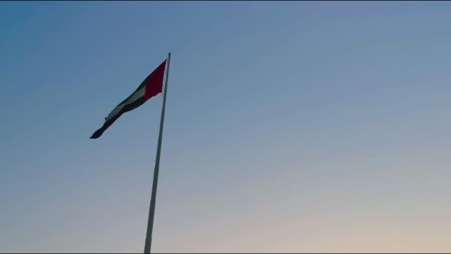 abu dabi şehir içinde sallayarak birleşik arap emirlikleri bayrağı - uae flag stok videoları ve detay görüntü çekimi