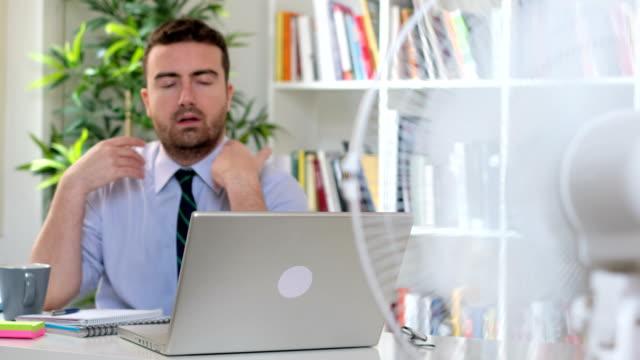 vidéos et rushes de la vidéo est sur un homme en sueur bureau essayant de régénérer - canicule