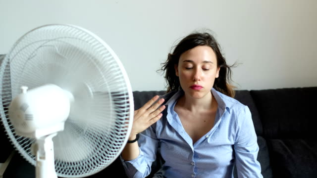 the video is about a young woman refreshing herself in front of a fan because of the summer heat - ritemprarsi video stock e b–roll